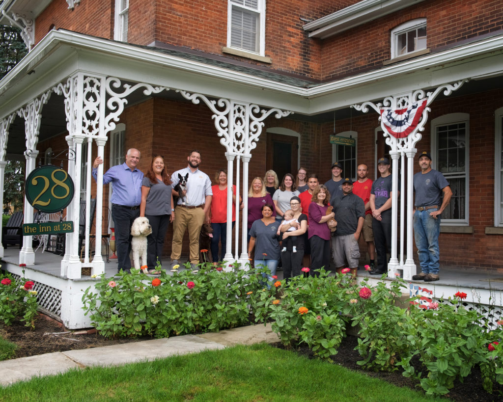 Several people standing on porch of large brick building with flowers in front