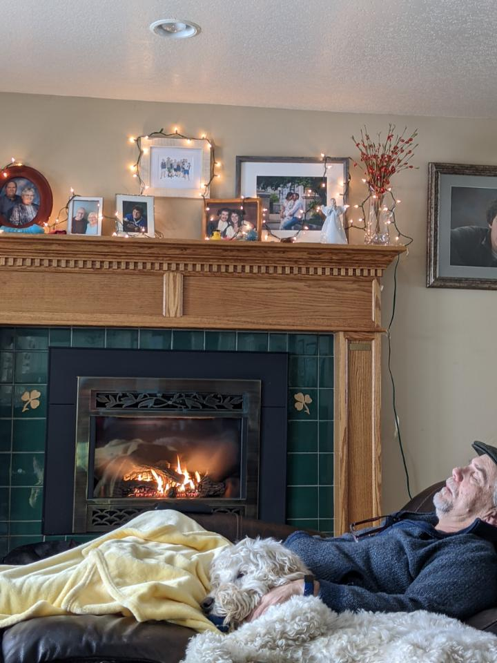 Man and dog sleeping by fireplace