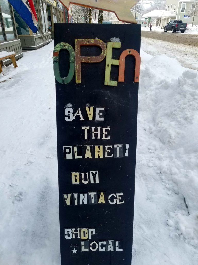 sign about saving the planet, shopping vintage and buying local