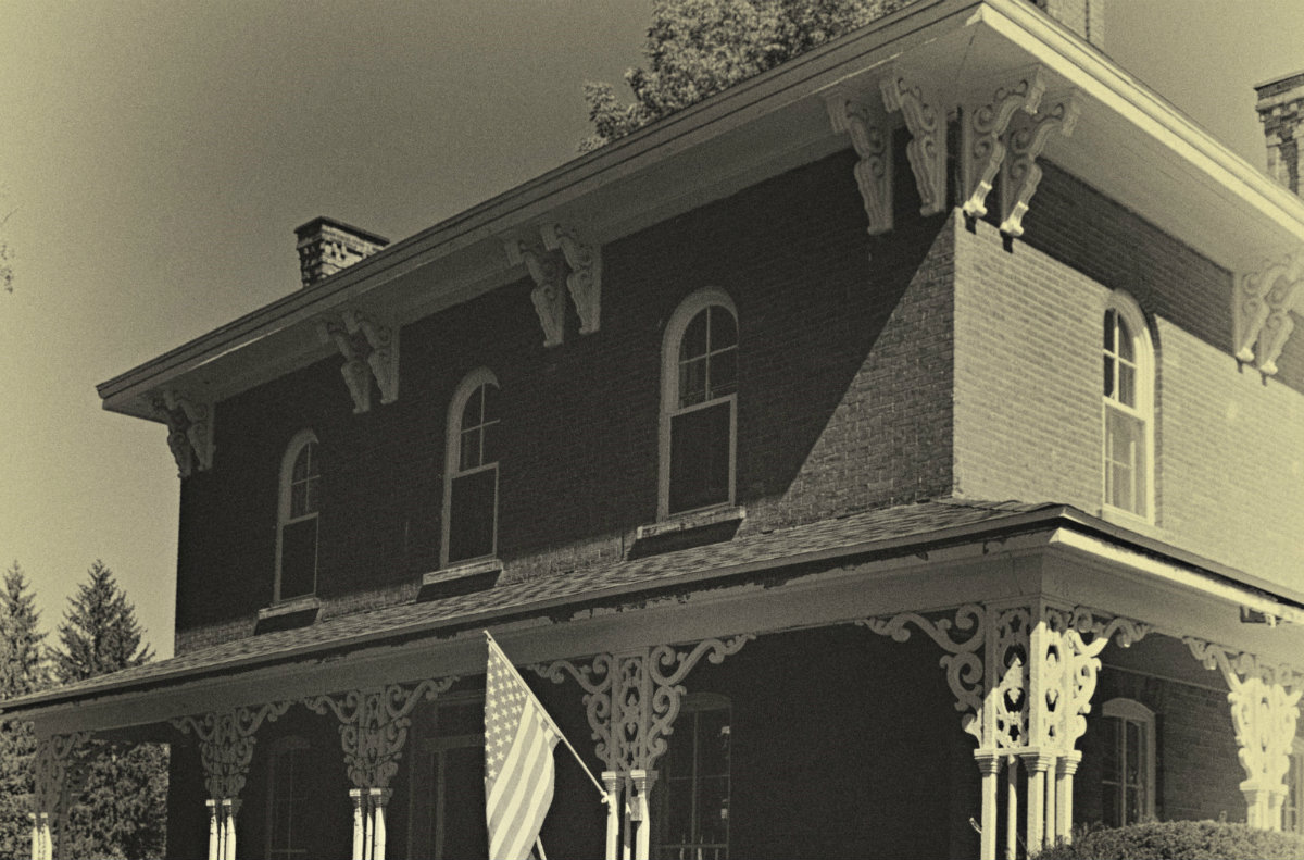 Old, faded view of historic, detailed brick home in black and white