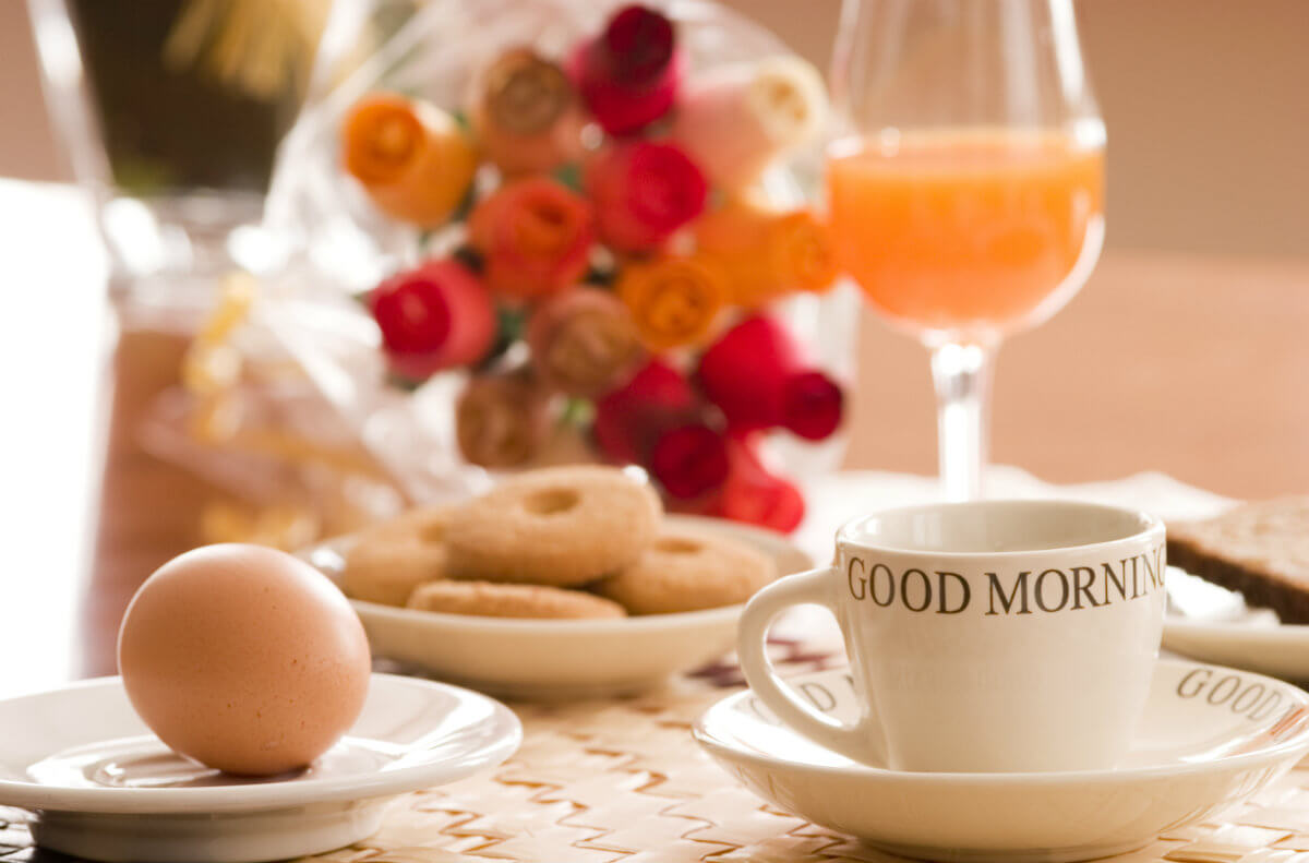 Breakfast table set with white cup, a whole, brown egg, donuts, glass of orange juice plus red and orange flowers