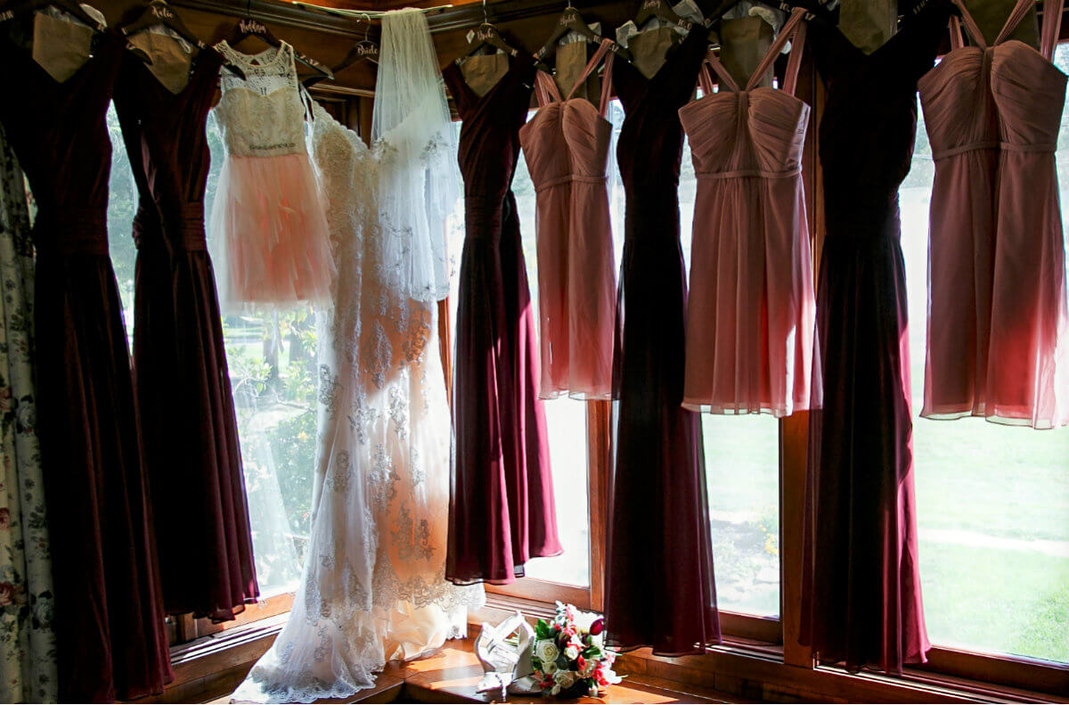 White wedding dress, six long burgundy dresses, three short pink dresses plus a pink and white dress hanging in windows
