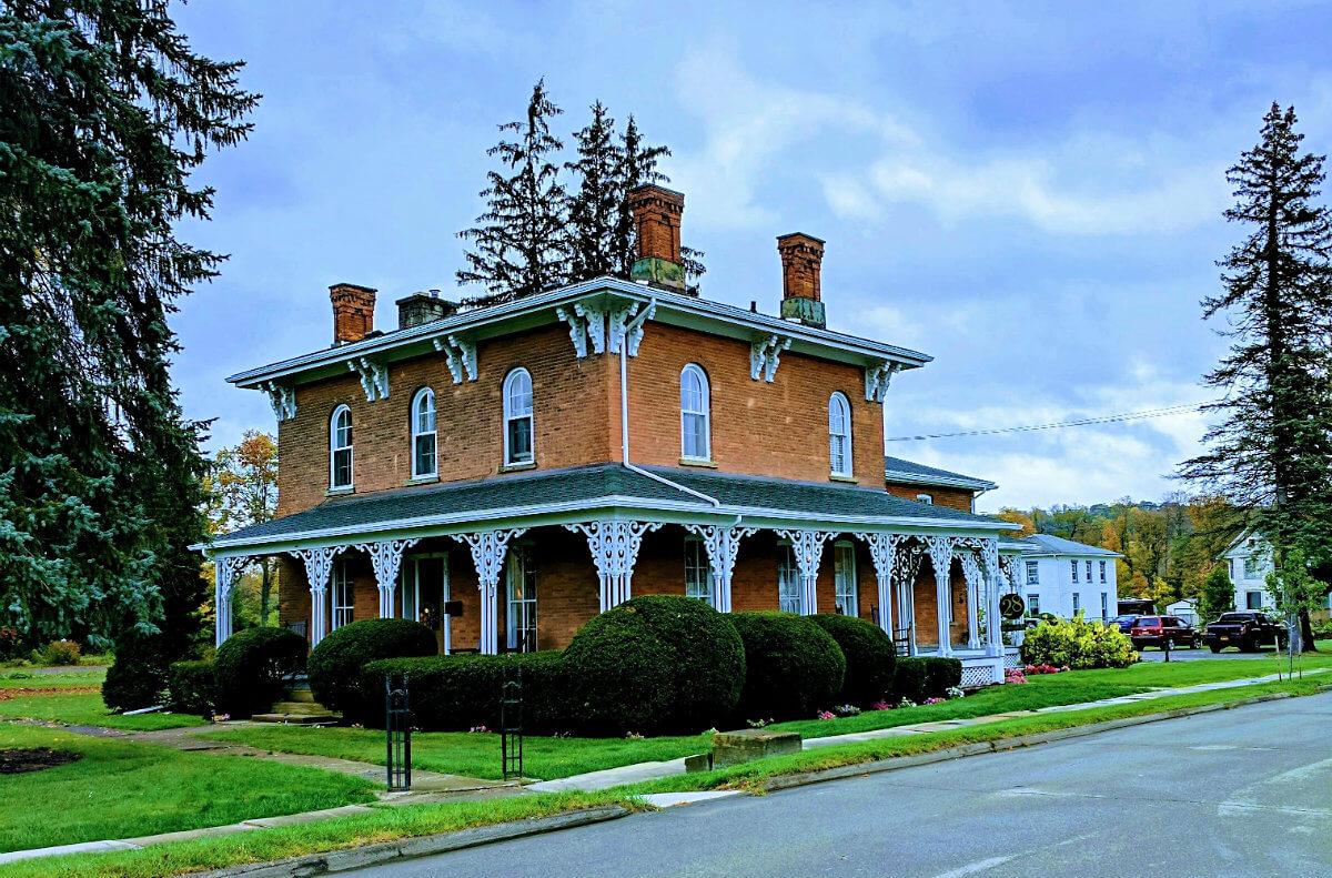 Outside of an inn with brown brick, white pillars, and green shrubs around the perimeter
