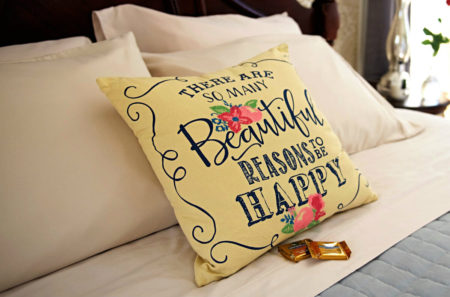 Four tan pillows behind cream pillow with blue words, there are so many beautiful reasons to be happy