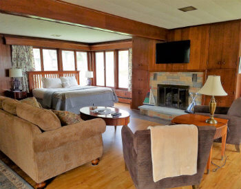 Large room with brown paneled walls with a tan couch, two brown chairs, a bed and stone fireplace