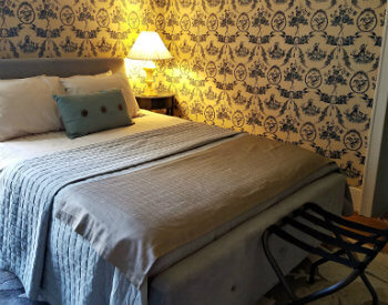 Bedroom with blue and white wallpaper, nightstand with bright light and a black luggage holder at the end of the bed