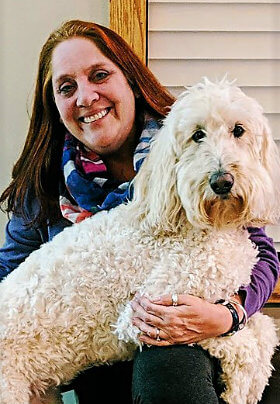 Smiling woman with blue and white scarf holding a large, white dog
