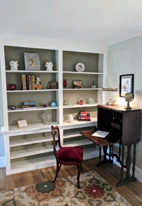 Large, white, built-in bookshelf and brown desk and chair