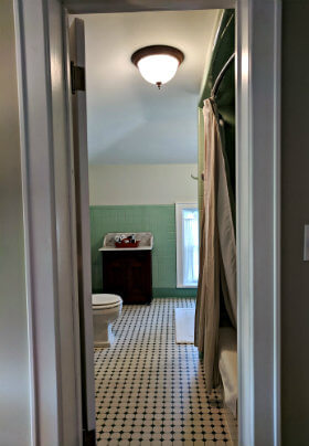 Bathroom with green wall with green and white, patterned floor tiles a bright light fixture