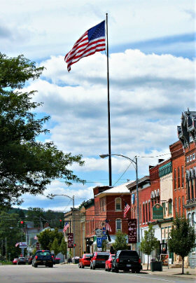 Main village street with several buildings, green trees and very tall flag pole with red, white and blue American flag