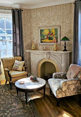 Seating area with ornate fireplace, gold patterned wallpaper and 2 chairs, one gold and one with grey design