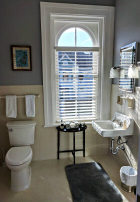 White bathroom with white fixtures, grey bathmat and a large arched window