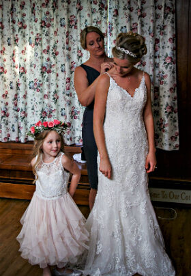 Woman in blue dress fastening white dress of a bride and a little girl standing beside them