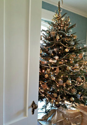 White door open showing a Christmas tree with silver, gold and white ornaments a bead garland