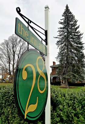 Green and gold sign with tall, pine tree and large, red brick home in the background
