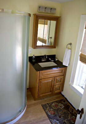 Bathroom with yellow walls, curved corner shower, patterned bathmat, mirror and brown vanity with black top