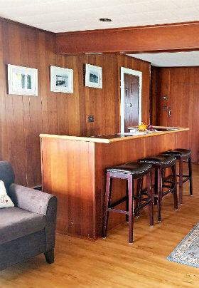 Room with brown paneled walls, brown bar and black bar stools