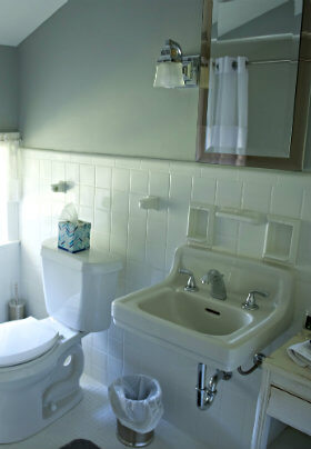Bathroom with white toilet and sink, a mirror and white tile and green walls